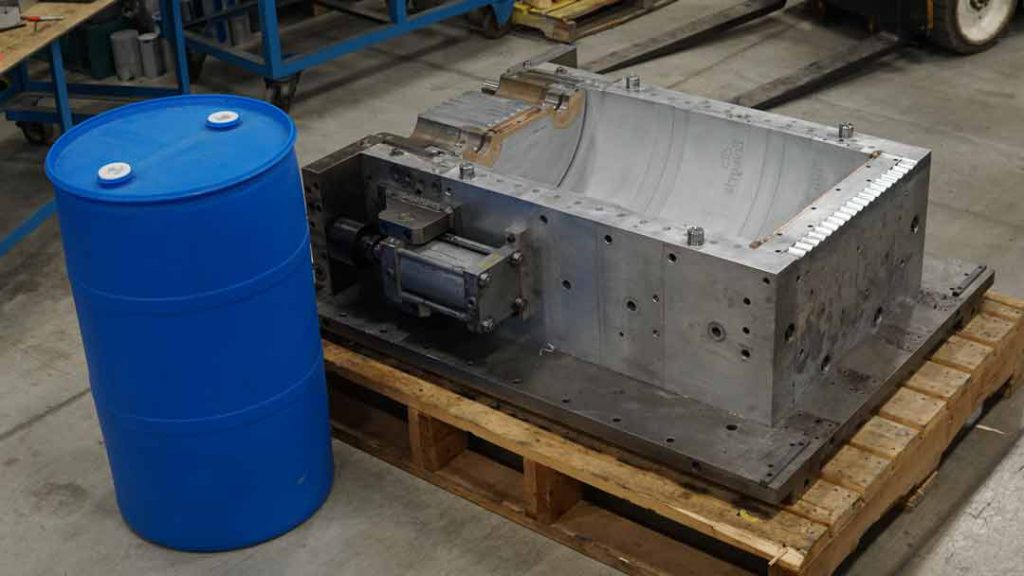 Industrial Plastic Drum next to extrusion blow mold.